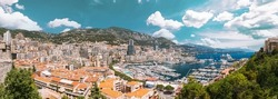 Monaco, Monte Carlo cityscape. Real estate architecture on mountain hill background. Many high-rise buildings in downtown area. Yachts moored at town quay In Sunny Summer Day. Altered Sky.