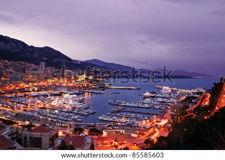 Monaco scenic at night including lavish yachts and the Monte Carlo skyline