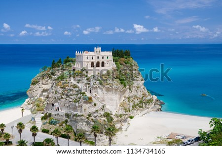 Monastery Sanctuary church of Santa Maria dell Isola on top of rock Tyrrhenian Sea and green palm trees, blue sky white clouds in summer clear day, Tropea town, Vibo Valentia, Calabria, Southern Italy #1134734165