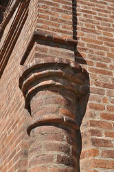 Monastery wall element. Semicircular stone column at the corner of the wall of the old monastery. Old brickwork.
