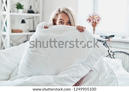 Monday morning. Attractive young woman covering half of her face with blanket and looking at camera while sitting in bed at home