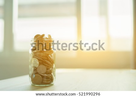 Money and banking concept with coins and jar glass for savings full of medal, dollar, token, piece, specie with filter effect retro vintage style