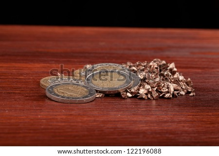 money and copper nuggets on wooden table and black background