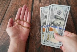 money and jewelry, pawn shop and buy and sell, golden chain or bracelet in hand on wooden background, closeup