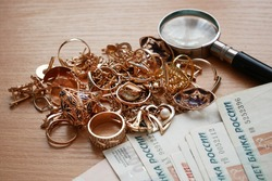money and jewelry, pawn shop and buy and sell golden rings, necklace bracelet o wooden background, closeup