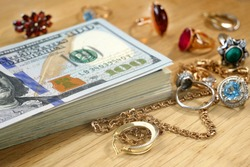 money and jewelry, pawn shop and buy and sell precious metals concept, golden rings, necklace bracelet o wooden background, closeup