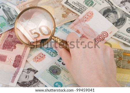 money and magnifier in hand enlarging banknote