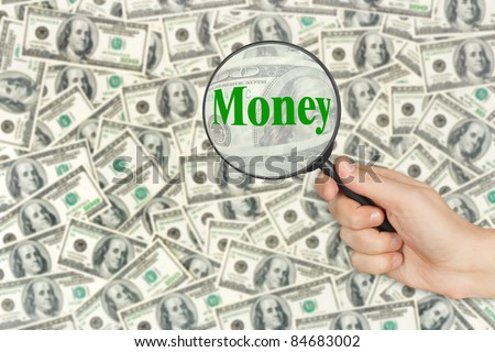 Money and magnifying glass in hand - business background