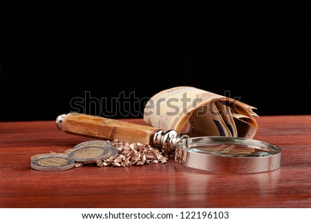 money and magnifying glass on wooden table and black background
