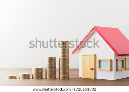 Money and miniature house. Finance and investment. Miniature house and stack of coins on wood table.