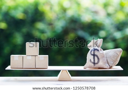 Money and supply concept : Money dollar bag and supply products on balance scale on wooden table depicts balancing between risk and return. Investment between money and supply reverse.