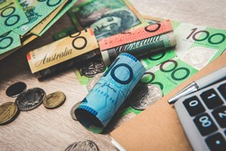 Money, Australian dollars (AUD), with notebook and calculator on the table - financial and investment concepts