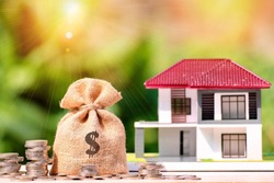 money bag and stack coin with flare , investment property, home insurance, savings plan for housing concept.