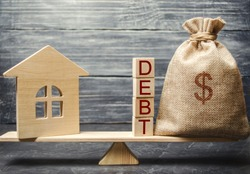 Money bag and wooden blocks with the word Debt and a miniature house on the scales. Payment of debt for real estate. Pay off the mortgage loan. Risks of buying a house. Buying an apartment on credit.