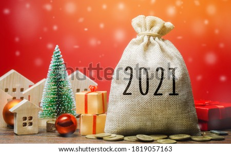 Money bag 2021, Christmas tree, miniature houses and gifts. New Year or Xmas winter holiday. Accumulating money and planning a budget. Business and finance. Loans, deposit, credit. Promotions, offers Foto stock ©