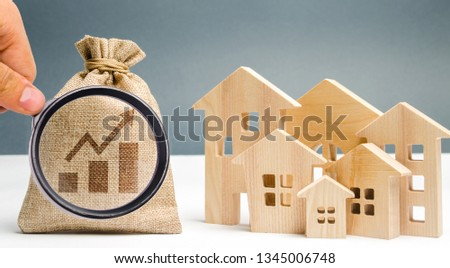 Money bag with chart up and wooden houses. The concept of real estate market growth. The increase in housing prices and rent. Growing demand for property purchase. Rising interest rates on mortgages
