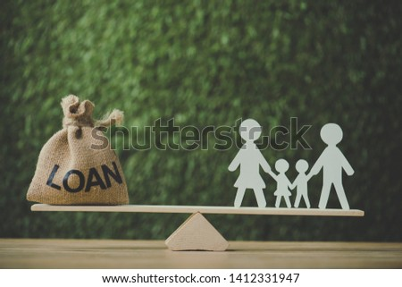 money bag with loan inscription and paper cut family balancing on see saw on green background