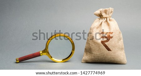 Money bag with rupee (rupiah) sign and magnifying glass. The concept of finding sources of investment and sponsors. Charitable funds. Startups and crowdfunding. Search for available loans. Find a job. #1427774969