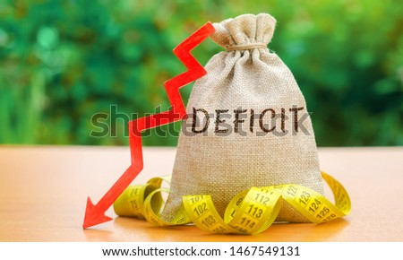 Money bag with the word Deficit and tape measure with down arrow. Budget deficit concept. Low profit. Financial costs. Bankruptcy. Adverse conditions in foreign markets. Capital outflow Foto stock ©