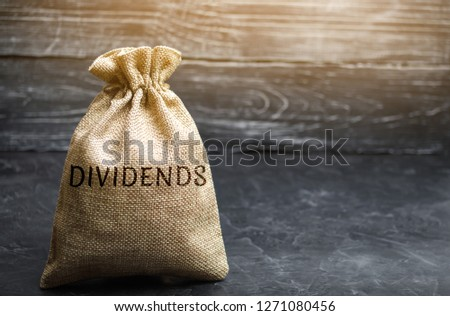 Money bag with the word Dividends. A dividend is a payment made by a corporation to its shareholders as a distribution of profits. Concept business finance and investment. Saving money. Dividend tax