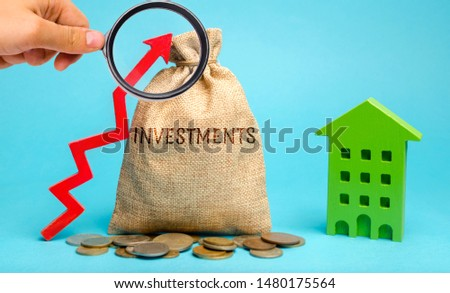 Money bag with the word Investments, up arrow and wooden house. The concept of investing in real estate construction. Effective investment. Buying apartments. Business and finance