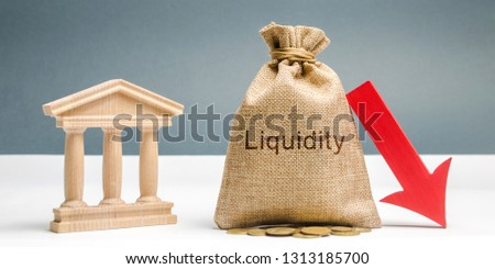 Money bag with the word Liquidity, down arrow and bank building. The concept of market decline. Drop in sales. Crisis and collapse. Failure to quickly sell assets at a price close to the market #1313185700