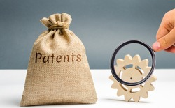 Money bag with the word Patents and a wooden gear. Registration of patents and copyright compliance. Licensing technology and scientific discoveries. Purchase and sale of patents. Royalties