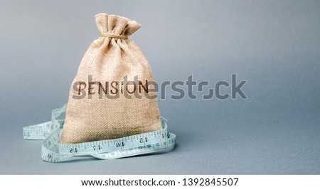 Money bag with the word Pension and tape measure. Fall / reduction pension payments. Retirement. Financing retirees. Reduction of the pension fund. The low size of pensions. Poverty. Lack of money #1392845507