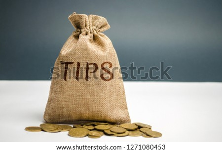 Money bag with the word Tips. Award for good service in the cafe / restaurant. A gratuity is a sum of money customarily given by a client or customer to a service worker in addition to the basic price Сток-фото ©