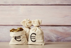 Money bags with euro coins on wooden background