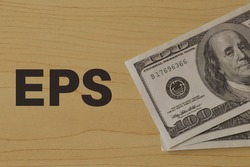 Money banknotes on the table with text EPS stands for EARNINGS PER SHARE