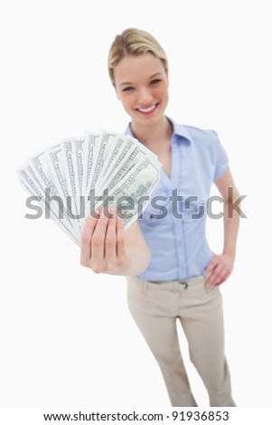 Money being held by woman against a white background