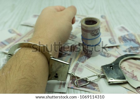 money bribe or corruption theme. male hands with dollars banknotes in handcuffs #1069114310