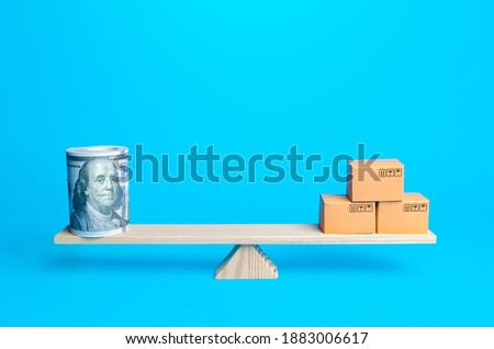 Money bundle of dollars and boxes on scales. Trade balance and purchasing power. Commerce and business. Minimum wage and living wage. Import and export duties, profit from sale of value added goods. Foto stock ©