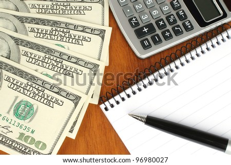 Money, calculator, notepad and pen on wooden background