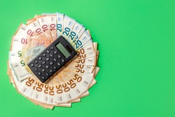 Money. Cash. Euro bill and calculator on the green background. The salary. Poverty and wealth concept. Money savings. Poor, rich. Copy space. High quality photo