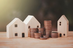 Money coin stack to show growing graph with house model,investment in the real estate business.Loans for purchase of residential houses.Save money and thinking plan for the future on wood.