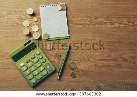 Money concept. Green calculator with coins and notebook on wooden table