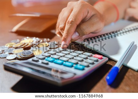Money concept Man using calculator to count money savings and living costs. Calculator with coins and notebook on wooden table.