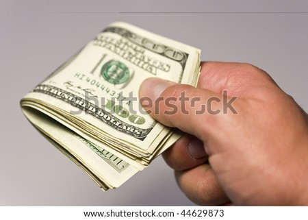 money concept with hand holding us dollars on white