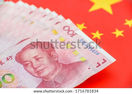 Money / currency of PBOC or people's bank of china. One hundred CNY Chinese yuan bill with a flag of China. 100 rmb or renminbi, depicts Beijing economy system, public banking policy and interest rate