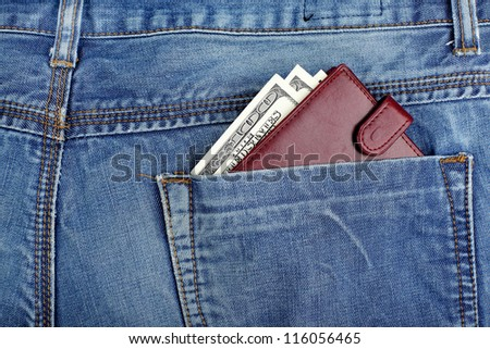 money dollars and brown leather wallet in jeans back pocket blue color background - stock photo