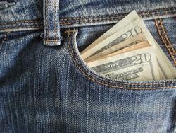 Money 20 dollars cash bank notes in denim jeans pocket.