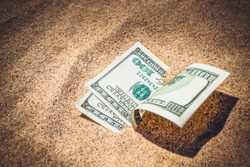 Money dollars half covered with sand lie on beach close-up. Dollar bills partially buried in sand. Three hundred dollars buried in sand on sea ocean beach Concept finance money holiday relax vacation
