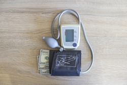 Money dollars lie with a tonometer on the table in the hospital. Expensive medicine and a tonometer apparatus lies on the table.