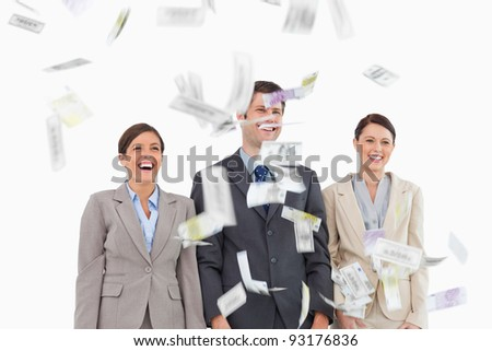 Money dropping down on smiling businessteam against a white background