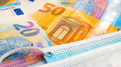 Money, EURO - EUR. Currency of the European Union. Euro banknotes and surgical masks. Close-up photo. Concept of Risk, Financial Crisis, debts in the midst of the COVID-19 pandemic.