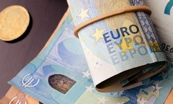 Money, EURO - EUR. Euro banknotes and coin on a dark  desk. Highlight for the 20 Euro note on a roll of money with rubber band. Photo with a view from above.