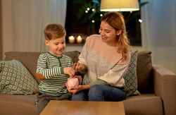 money, family and people concept - happy smiling mother and thrifty little son putting euro coin to piggy bank at home