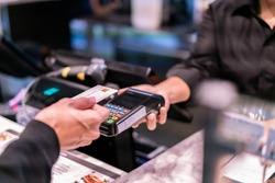 Money,Financial and pay technology concept.Business man holding credit card reader machine and customer paying money with contactless credit card with NFC technology to pay.